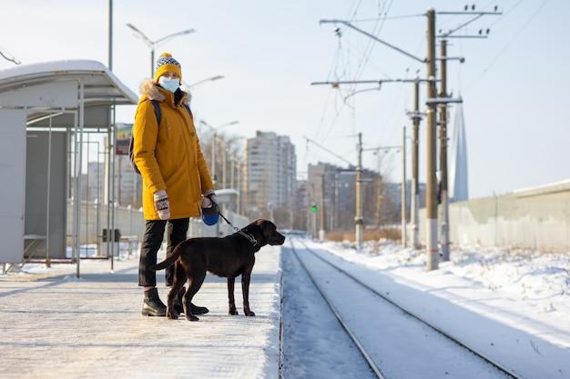 Kaukasische frau in einer gelben jacke mit medizinischer maske mit einem labrador-retriever-hund, der auf einen zug wartet