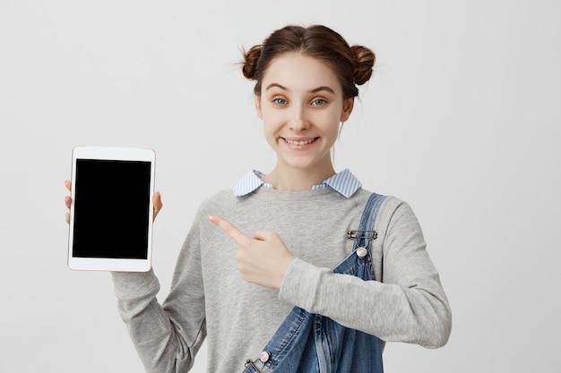 Kaukasische frau in lässigem denim, die moderne trendige techniken in ihrer hand mit lächeln demonstriert. headshot einer glücklichen kundin, die sich mit dem lang erwarteten kauf zufrieden fühlt. marketing, vertrieb