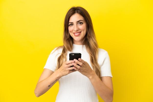 Kaukasische frau isoliert auf gelbem hintergrund, die in die kamera schaut und lächelt, während sie das handy benutzt