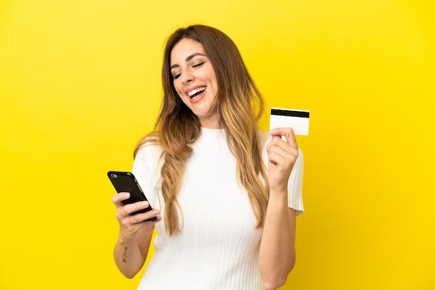 Kaukasische frau isoliert auf gelbem hintergrund, die mit dem handy mit einer kreditkarte kauft