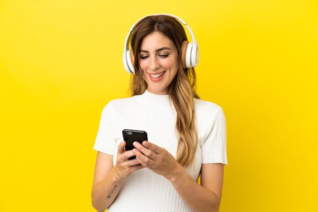 Kaukasische frau isoliert auf gelbem hintergrund musik hören und handy suchen