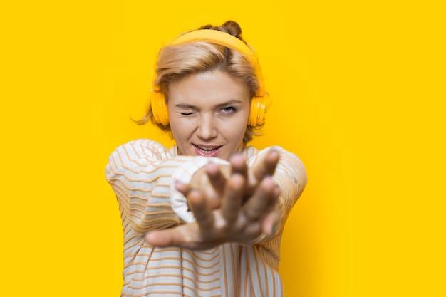 Kaukasische frau mit blondem haar, das musik auf einer gelben wand unter verwendung von kopfhörern hört