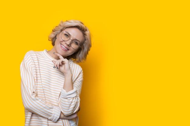 Kaukasische frau mit blonden haaren und brillen, die kinn berühren und auf einer gelben wand mit freiem raum aufwerfen
