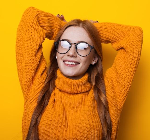 Kaukasische frau mit brille und sommersprossen, die kamera in einem gestrickten gelben pullover lächeln