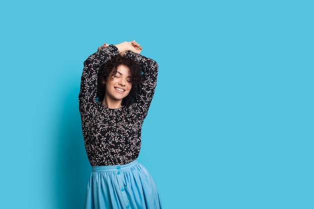 Kaukasische frau mit dem lockigen haar, das auf einer blauen wand aufwirft, während ihre hände aufsteigt