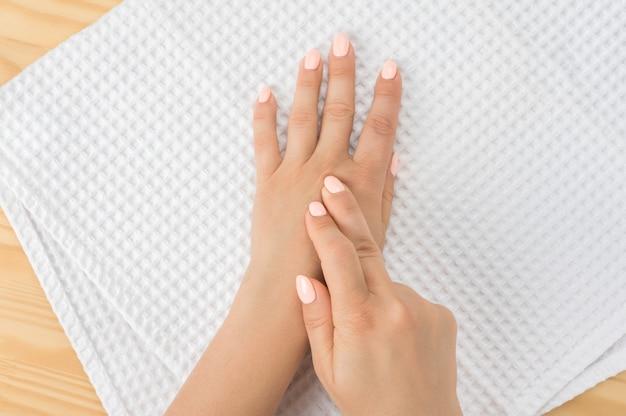 Kaukasische frau mit der hand auf ihrem ungesunden finger und handfläche. selbstmassage-bürosyndrom und muskelschmerzen nahaufnahmehand der person massiert ihre hand vor schmerzen in gesundem konzept akupressur-selbstmassage