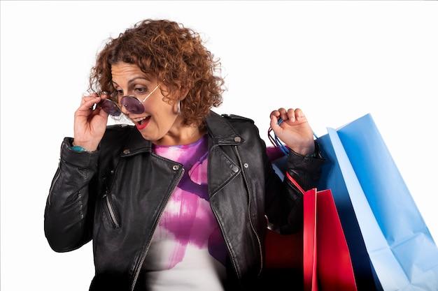 Kaukasische frau mit der sonnenbrille, die unten, mit einkaufstaschen überrascht schaut