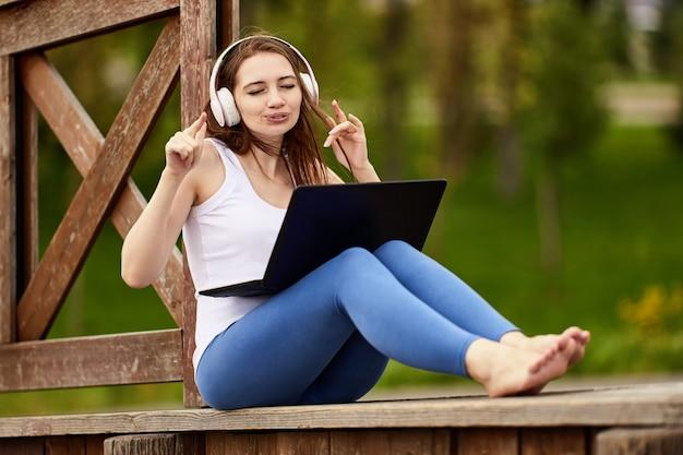 Kaukasische frau mit laptop hört musik über drahtlose kopfhörer im öffentlichen park