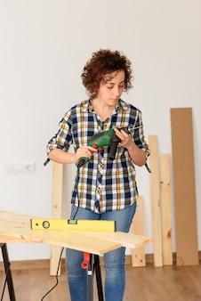 Kaukasische frau mit lockigem haar hält einen bohrer in ihren händen, bereit, heimwerkerarbeiten vorzunehmen.