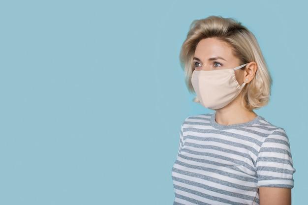 Kaukasische frau mit medizinischer maske auf gesicht und blonden haaren wirbt etwas auf einer blauen studiowand