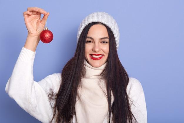 Kaukasische frau mit rotem weihnachtsball in den händen, steht lächelnd isoliert über blauer wand, brünette frau, die warmen weißen pullover trägt