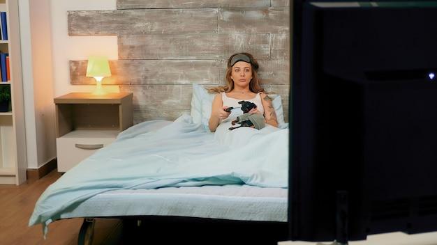 Kaukasische frau mit schlafmaske und pyjama vor dem fernseher.