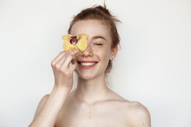 Kaukasische frau mit sommersprossen und roten haaren, die ihr auge mit einer blume bedecken, lächelt mit nackten schultern auf einer weißen studiowand