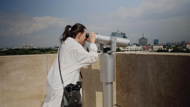 Kaukasische frau mit teleskop vom beobachtungspunkt aus