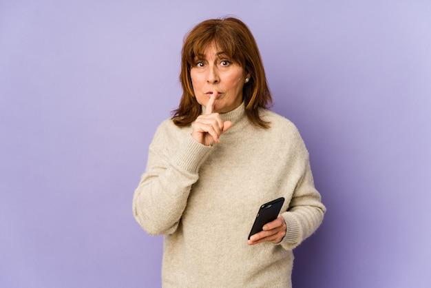 Kaukasische frau mittleren alters, die ein telefon hält, das ein geheimnis hält oder um stille bittet.