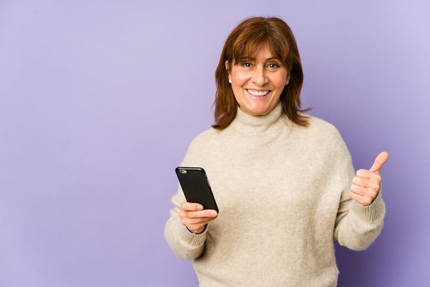 Kaukasische frau mittleren alters, die ein telefon hält, das lächelt und daumen hochhebt