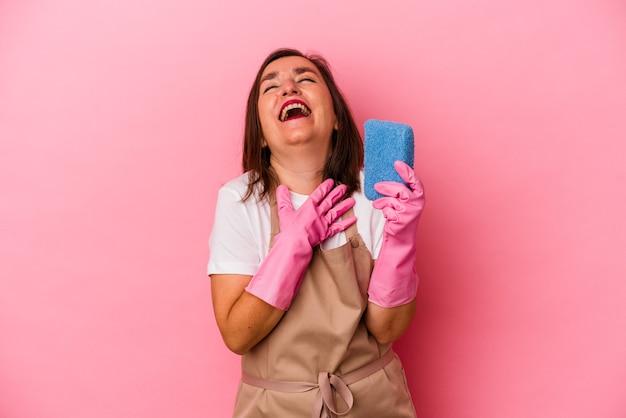 Kaukasische frau mittleren alters, die nach hause isoliert auf rosafarbenem hintergrund putzt, lacht laut und hält die hand auf der brust.