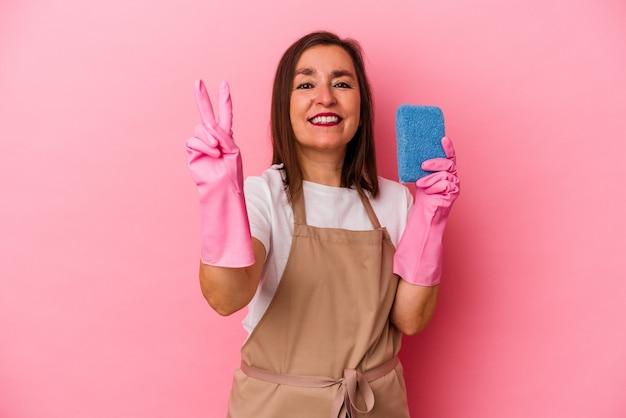 Kaukasische frau mittleren alters, die nach hause putzt, isoliert auf rosa hintergrund, die nummer zwei mit den fingern zeigt.