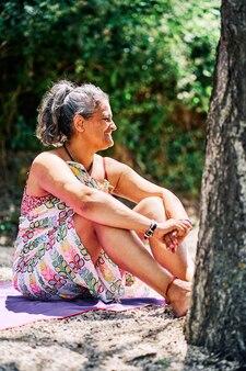 Kaukasische frau mittleren alters mit weißem haar lächelnd auf dem feld sitzend