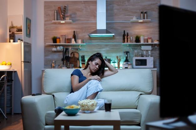 Kaukasische frau schläft zu hause auf dem sofa beim fernsehen ein. müde erschöpfte, einsame, verschlafene hausfrau im schlafanzug, die vor dem fernseher schläft und auf einer gemütlichen couch im wohnzimmer sitzt.