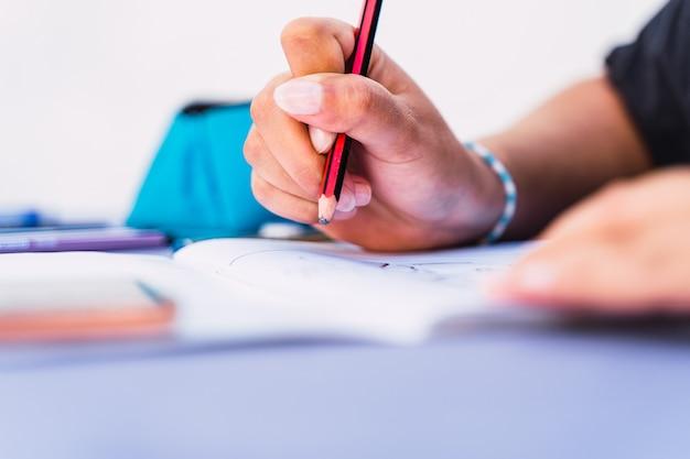 Kaukasische frau schreibt und zeichnet in einem notizbuch mit einem bleistift