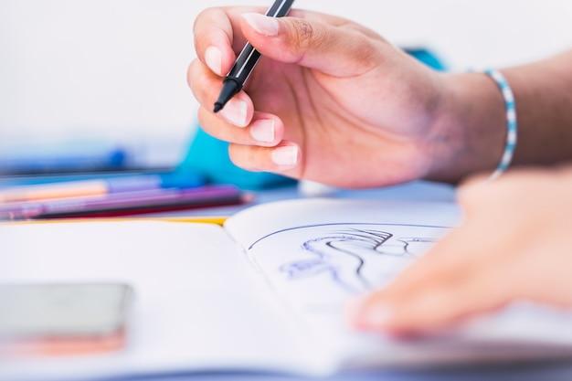 Kaukasische frau schreibt und zeichnet in einem notizbuch mit einem stift