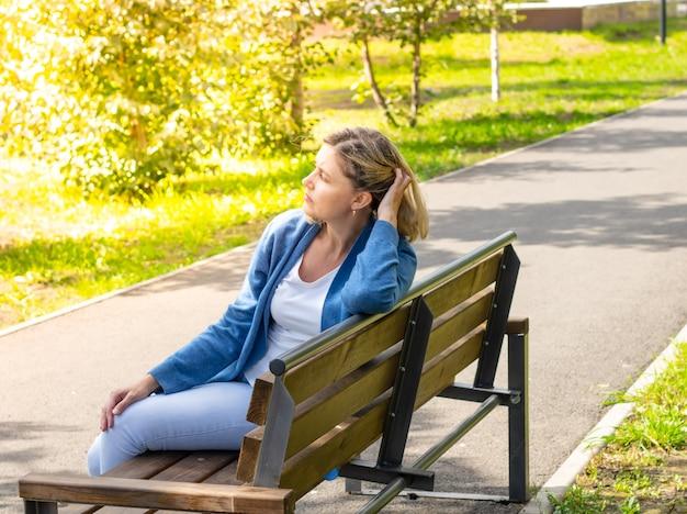 Kaukasische frau sitzt an einem sonnigen tag im park auf einer bank und bürstet ihr haar mit der hand