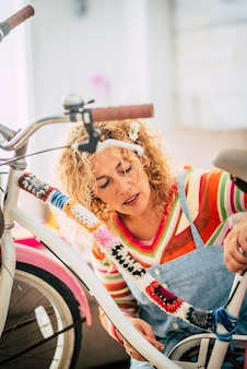 Kaukasische frau zu hause kreiert ein boho-farbiges glückliches fahrrad mit recycelten stücken