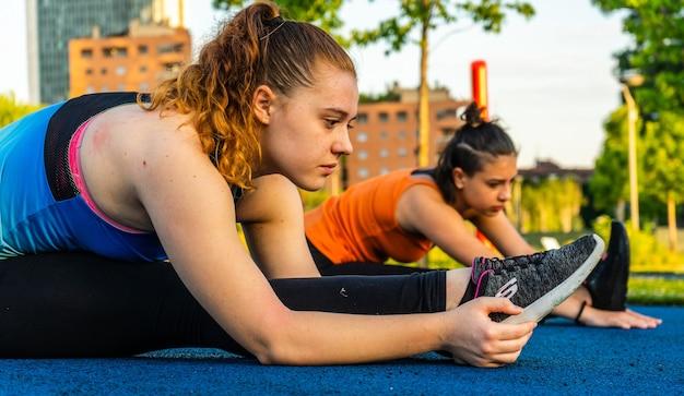 Kaukasische frauen, die sportbekleidung tragen und sich während des trainings im freien dehnen