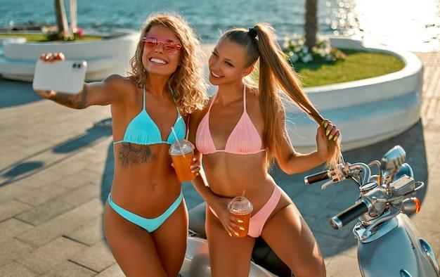 Kaukasische frauen in bikini-badebekleidung haben spaß daran, selfie auf dem smartphone in der nähe von fahrrad am strand an einem sonnigen tag zu nehmen.