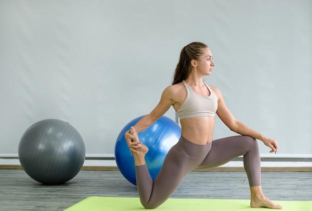 Kaukasische frauenübung, die die yoga-pose macht, die sich zu hause ausdehnt