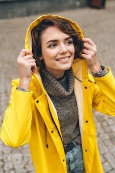 Kaukasische fröhliche frau in tragender haube des gelben regenmantels an und wetter beim gehen in stadtpark genießend