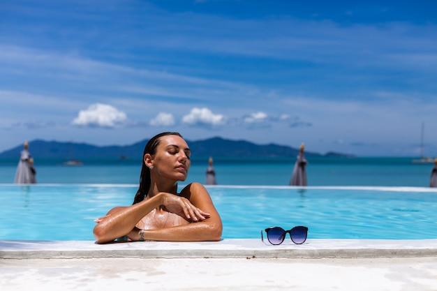 Kaukasische gebräunte frau glänzende bronzehaut durch pool im blauen bikini am sonnigen tag