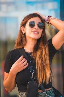 Kaukasische geschäftsfrau des schönen jungen brunette außerhalb des bürogebäudegehens. mit grünem rock und sonnenbrille auf der suche nach den seiten