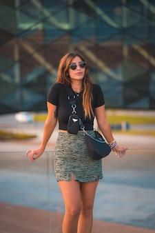 Kaukasische geschäftsfrau des schönen jungen brunette außerhalb des hintergrundbürogebäudes. mit grünem rock und sonnenbrille zu fuß