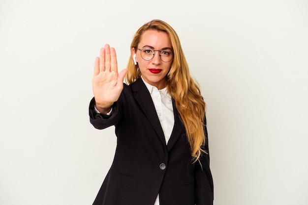 Kaukasische geschäftsfrau, die einen drahtlosen kopfhörer trägt, der auf weißem hintergrund steht, der mit ausgestreckter hand mit stoppschild steht und sie verhindert