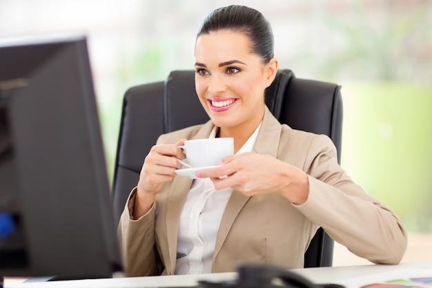 Kaukasische geschäftsfrau, die tee vor computer trinkt