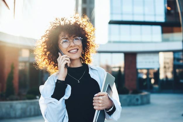Kaukasische geschäftsfrau mit den lockigen haaren, die eine telefondiskussion hat, während sie mit brillen und modernen geräten vor einem gebäude posiert