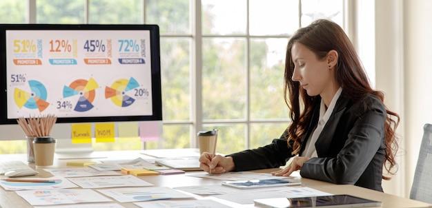 Kaukasische geschäftsfrau mitarbeiter mitarbeiter sitzen vorbereitung schreiben analyse statistik finanzinvestitionsförderung daten diagramm diagramm informationen papierkram dokumente im büro konferenzraum.