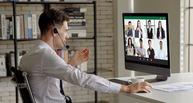 Kaukasische geschäftsmann mitarbeiter mitarbeiter tragen headset-mikrofon sitzen und diskutieren besprechungen über videoanruf-telekonferenzen mit kollegen, kunden und kunden im heimbüro während der quarantäne.