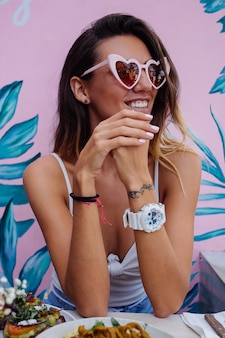 Kaukasische glückliche frau, die gesundes frühstück im café auf hintergrund der rosa tropischen wand hat. herz trendige sonnenbrille.