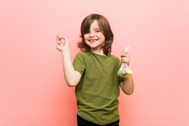 Kaukasische haltene süßigkeiten des kleinen jungen, die mit dem zeigefinger weg freundlich zeigen lächeln.