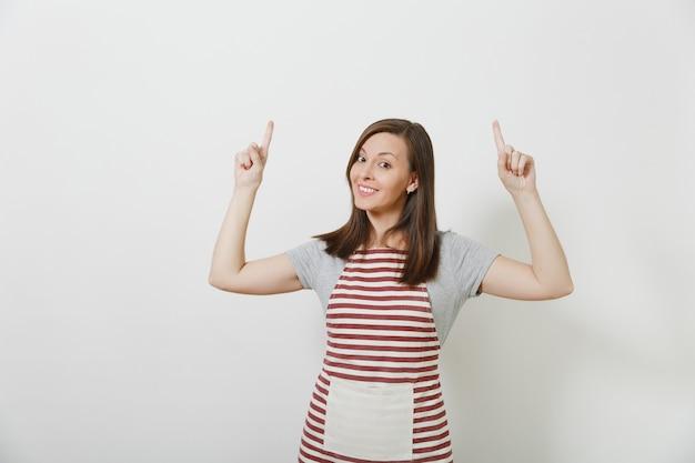 Kaukasische hausfrau des jungen attraktiven lächelnden brunette in der gestreiften schürze lokalisiert. schöne haushälterin, die zeigefinger nach oben zeigt
