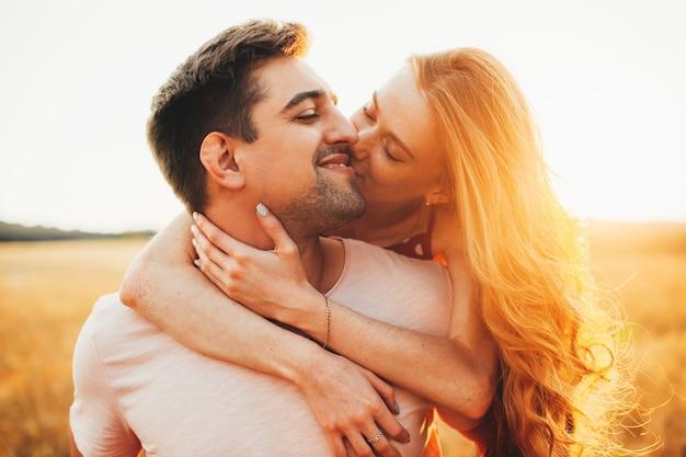 Kaukasische ingwerdame umarmt ihren geliebten, küsst ihn und lächelt während eines sonnenuntergangs auf dem feld