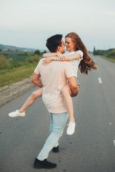 Kaukasische ingwerfrau umarmt ihren geliebten und lächelt sich auf der straße an