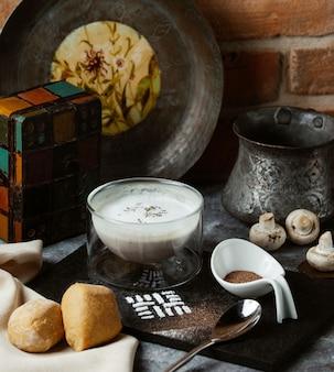 Kaukasische joghurtsuppe mit kräutern auf der oberseite innerhalb der transparenten schüssel und mit brotbrötchen gedient