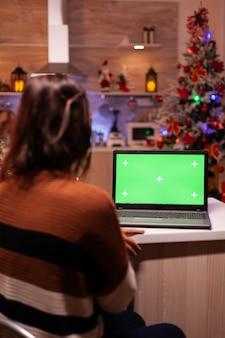 Kaukasische junge frau, die grünen bildschirm auf laptop betrachtet
