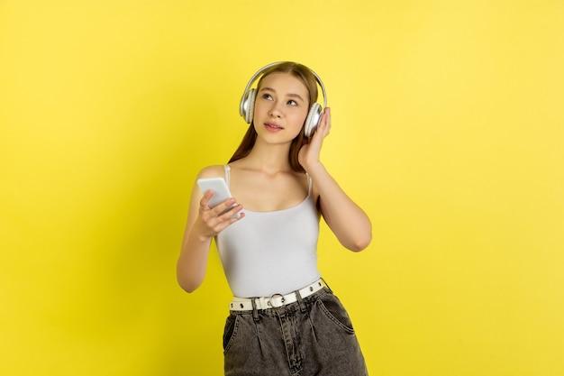 Kaukasische junge frau, die musik auf gelber wand hört