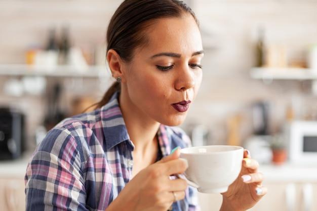 Kaukasische junge frau, die versucht, heißen grünen tee zu trinken