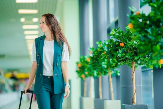 Kaukasische junge frau ein flughafenaufenthaltsraum, der auf das verschalen wartet